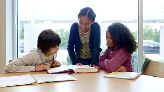 three middle school students study together in school library - junior high stock videos & royalty-free footage