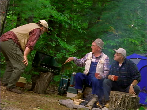 canted three middle-aged men grilling on portable stove in campsite - hochgekrempelte ärmel stock-videos und b-roll-filmmaterial
