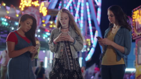 three millennial frenemies ignore each other and use their phones at a carnival - public celebratory event stock videos & royalty-free footage