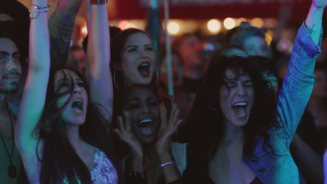 three millennial hipster women scream and cheer together at a popular music festival on the front row - estatico video stock e b–roll