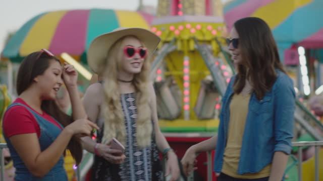 three millennial women gossip waiting in line for a ride at a summer carnival - millennial generation video stock e b–roll