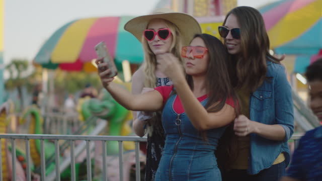 stockvideo's en b-roll-footage met three millennial women taking selfies waiting in line for a ride at a summer carnival - zelfportret fotograferen