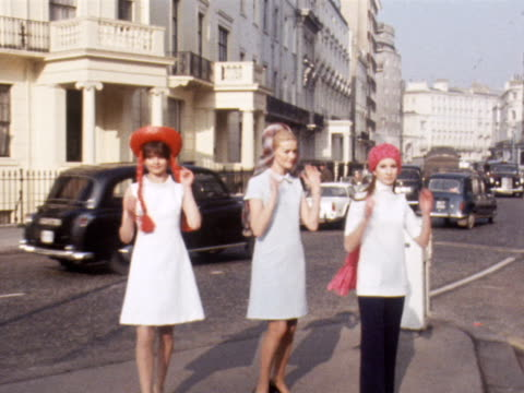 three models demonstrate hats with scarves attached to them in a london street 1969 - 1960 1969 video stock e b–roll
