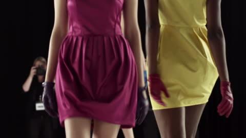 three models walking on catwalk with photographers - sfilata di moda video stock e b–roll
