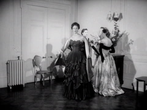 vidéos et rushes de three models wear ball gowns one of the models walks forward and poses for the camera 1953 - châle