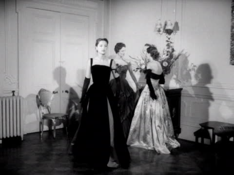 three models wear ball gowns. one of the models walks forward and poses for the camera. 1953. - england stock videos & royalty-free footage
