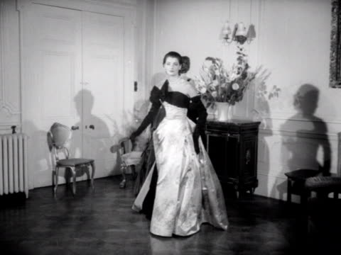 three models wear ball gowns one of the models walks forward and turns for the camera 1953 - evening gown stock videos & royalty-free footage