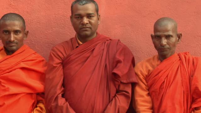 slo mo ms pan three monks standing against wall / bodh gaya, bihar, india - religion stock videos & royalty-free footage