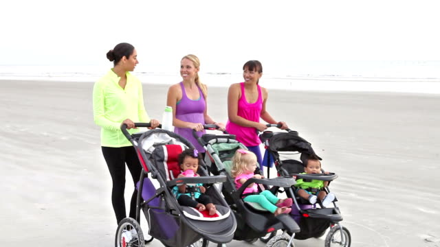 three mothers walking together with baby strollers - babies in a row stock videos & royalty-free footage