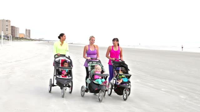 vídeos y material grabado en eventos de stock de tres madres caminando junto con cochecitos de bebé - cochecito de bebé