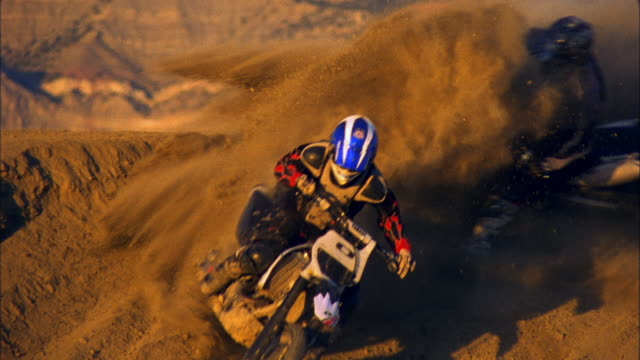 SM HA WS Three motocross riders driving on dirt hill in desert / Colorado, USA