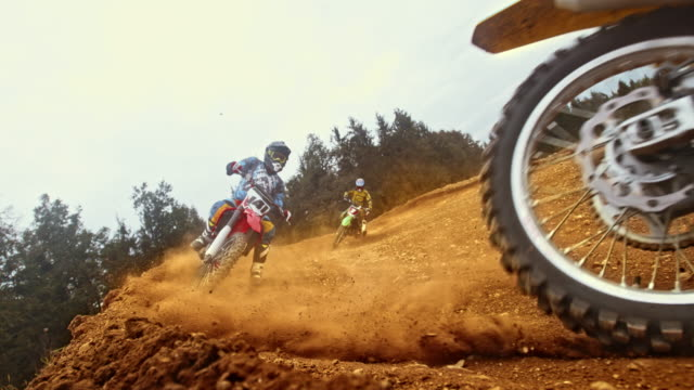 slo mo three motocross riders riding a turn on dirt trail - gara off road video stock e b–roll