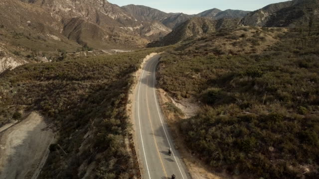 vídeos de stock, filmes e b-roll de três motociclistas dirigindo na angeles crest highway - antena drone tiro - angeles national forest