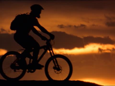 three mountain bikers ride across sunset - 若い男性だけ点の映像素材/bロール