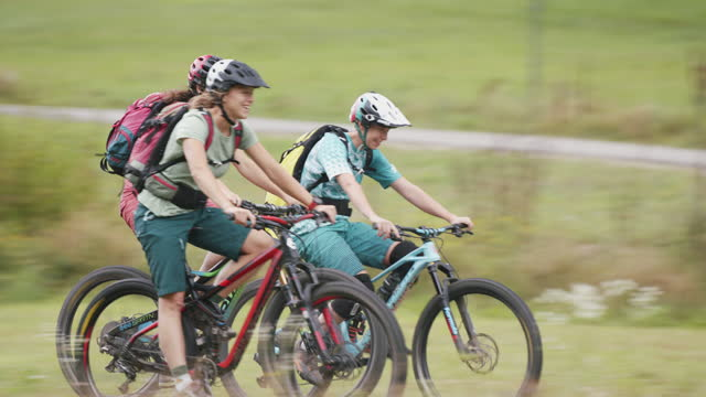 vídeos de stock e filmes b-roll de three mountain bikers riding up a hill in farmland - amizade feminina