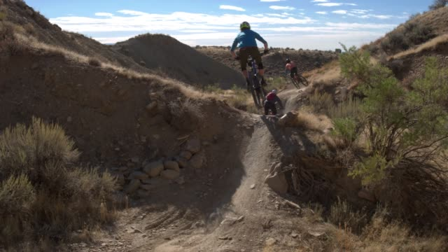 three mountain bikers with a dog jump on 18 road in fruita, colorado - bicycle trail outdoor sports stock videos & royalty-free footage
