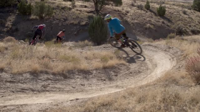 three mountain bikers with a dog ride around a curved trail on 18 road in fruita, colorado - andare in mountain bike video stock e b–roll