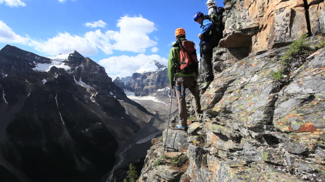 Three mountaineers climb steep rock face, take picture with cell