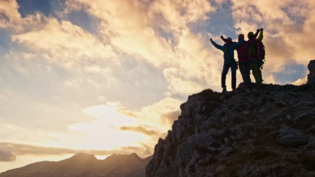 Three mountaineers doing a high five on mountain top at sunset