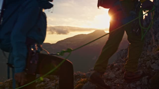 vídeos de stock e filmes b-roll de three mountaineers in a rope team walking up the mountain slope at sunrise - cordilheira montanha