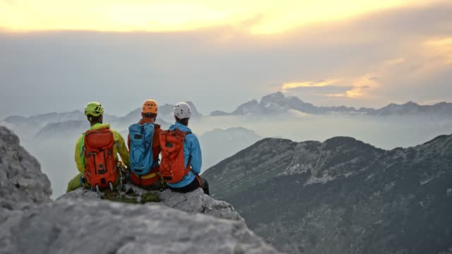 three mountaineers sitting on the edge of the mountain and talking while enjoying the view - wide shot stock videos & royalty-free footage