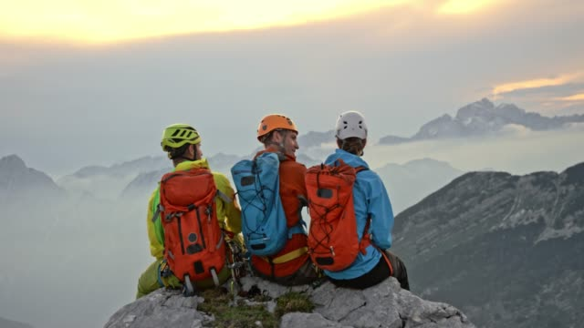 three mountaineers sitting on the edge on the mountain top and talking - mountaineering stock videos & royalty-free footage
