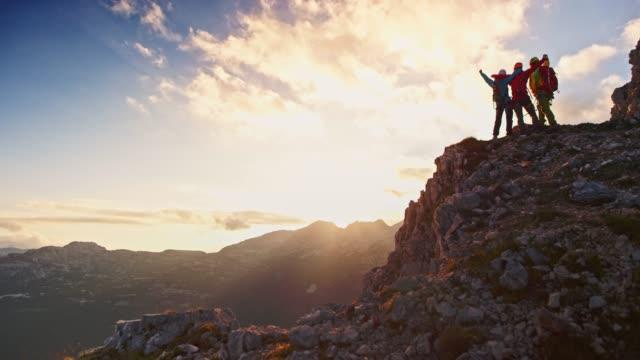 vidéos et rushes de trois alpinistes debout sur le sommet de la montagne et la célébration - aventure