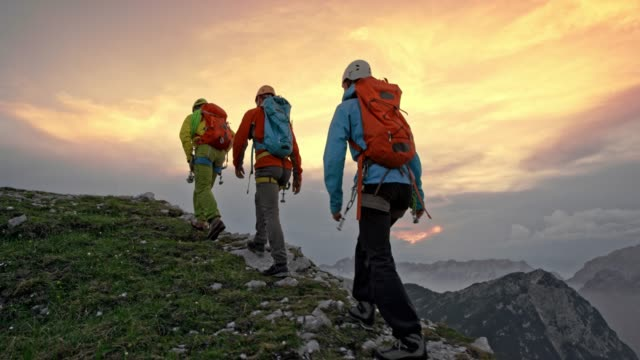 three mountaineers walking on a mountain ridge at sunset - hiking stock videos & royalty-free footage