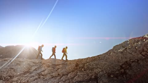 three mountaineers walking on a rocky mountain ridge in sunshine - hiking stock videos & royalty-free footage