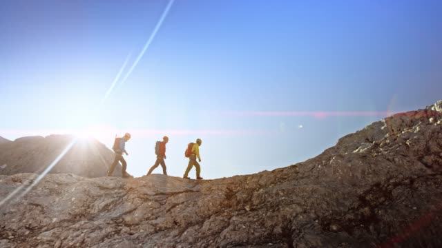 vídeos de stock e filmes b-roll de three mountaineers walking on a rocky mountain ridge in sunshine - grupo de pessoas