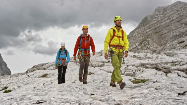 drei bergsteiger zu fuß auf einer bergigen gelände bei bewölktem wetter - gemeinsam gehen stock-videos und b-roll-filmmaterial