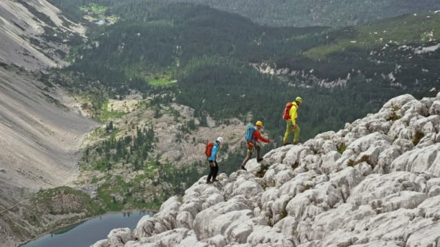 Three mountaineers walking on a rugged mountain slope in sunshine