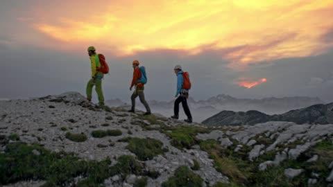 vidéos et rushes de trois alpinistes marchant sur le sommet de la montagne au coucher du soleil - trois personnes