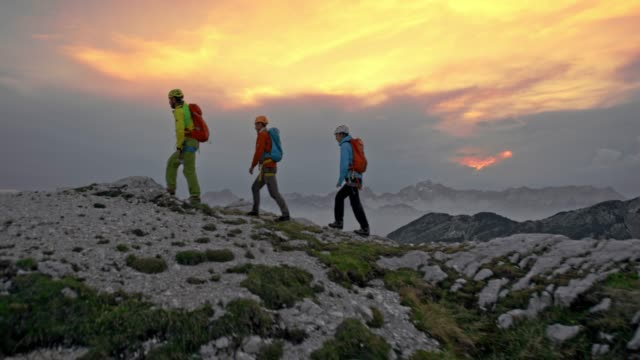 Three mountaineers walking on the mountain top at sunset