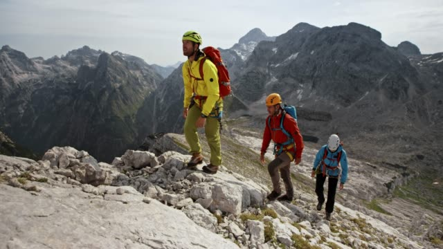 three mountaineers walking up a rocky mountain slope in sunshine - alpinismo video stock e b–roll