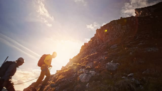 three mountaineers walking up the mountain at sunset - climbing rope stock videos & royalty-free footage