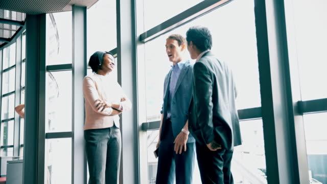 DS Three multi-ethnic businesspeople talking in the corridor