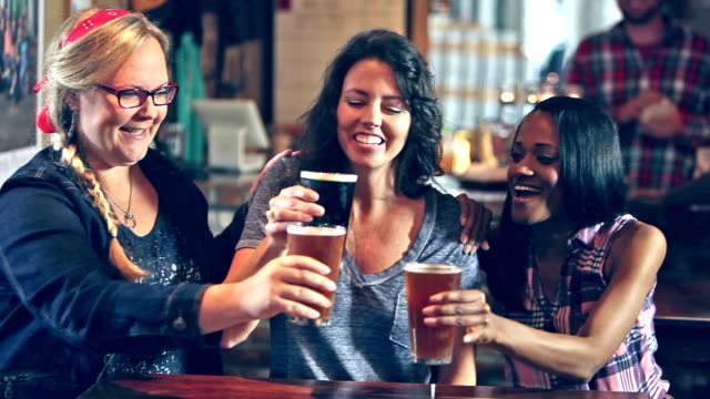 three multi-ethnic girlfriends drinking beer in bar - drinking beer stock videos and b-roll footage