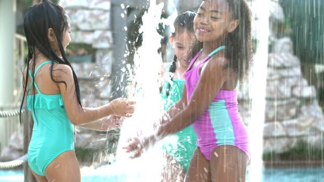 stockvideo's en b-roll-footage met drie multi-etnische meisjes spelen in water fonteinen - 6 7 years