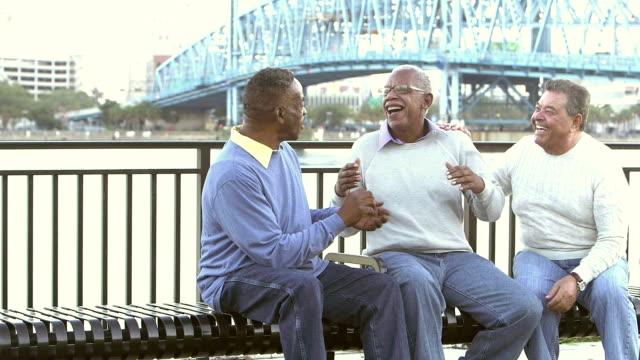 drei multi-ethnischen senioren herren am park bank sprechen - sitzbank stock-videos und b-roll-filmmaterial