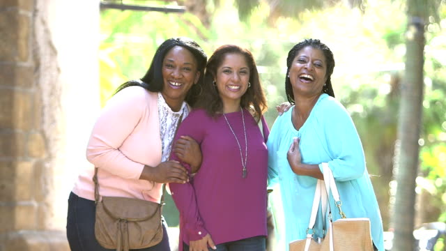Three multi-ethnic women, friends, smiling at camera