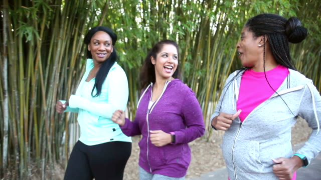 Three multi-ethnic women power walking in park