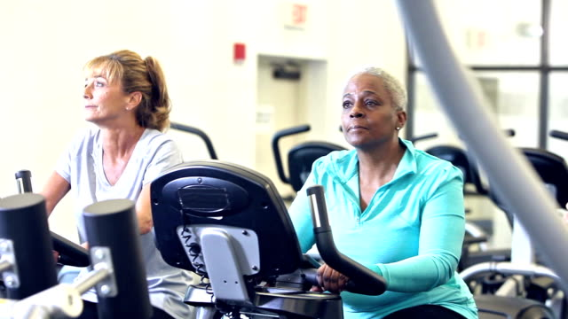 Three multi-ethnic women riding exercise bikes in gym