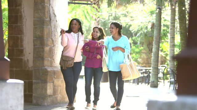 Three multi-ethnic women walking, friends hanging out