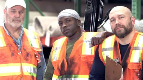 vídeos y material grabado en eventos de stock de tres trabajadores y multiétnicos en el almacén de alfombras - típico de la clase trabajadora