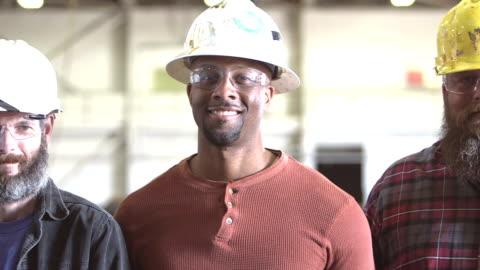 drei multi-ethnischen arbeiter tragen schutzhelme - manufacturing occupation stock-videos und b-roll-filmmaterial