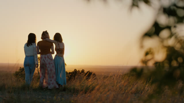 WS SLO MO. Three nature girls stand in field on mountainside at sunset.