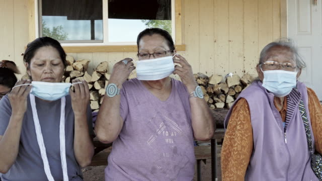 three navajo women putting on their masks to protect them from covid19 - north american tribal culture stock videos & royalty-free footage