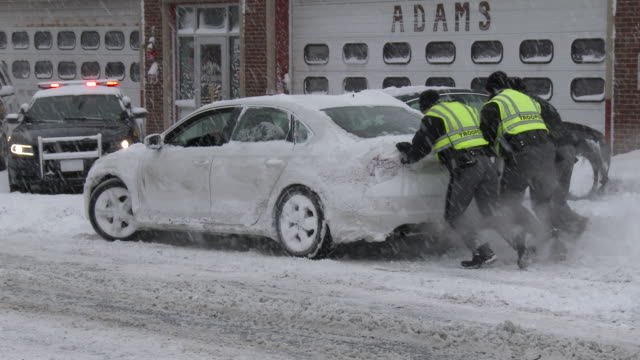 three new york state troopers help push a stranded motorist out of deep snow on main street in adams new york - scott mcpartland stock videos and b-roll footage