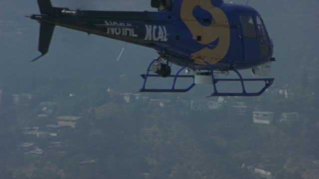 three news radio station helicopters fly over the city of los angeles. - luftfahrtindustrie stock-videos und b-roll-filmmaterial